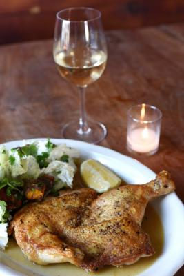 Brick chicken dinner with a glass of white wine